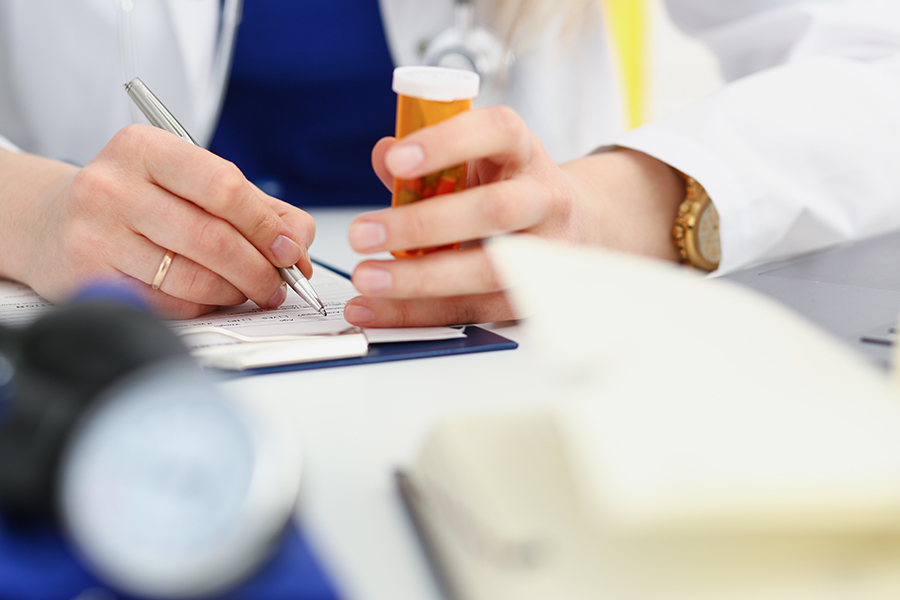 Female medicine doctor hand hold jar of pills